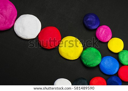 Mixed colors, different size circles on the dark surface of the table