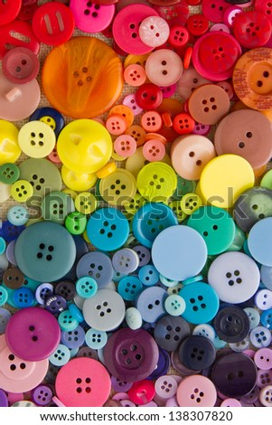 Mixed coloured bright buttons, arranged in rainbow colour formation, filling the frame - stock photo
