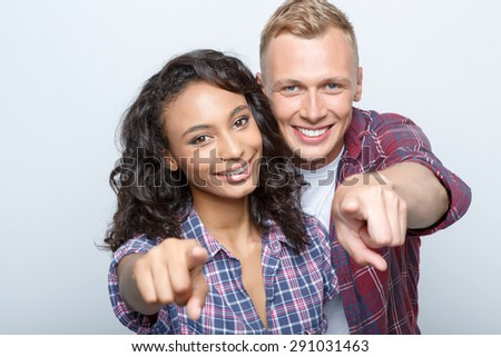 Mixed couple. Beautiful young mulatto girl and her blond boyfriend standing near embracing smiling and pointing at you, isolated on grey background