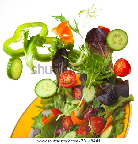 Mixed Crisp Salad being tossed in the air - stock photo