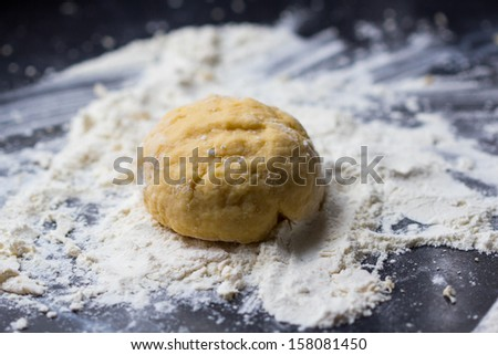 Mixed dough for Italian pasta or pizza on table - stock photo
