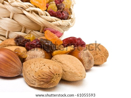 Mixed dried fruits and nuts spilling from basket on white background. - stock photo