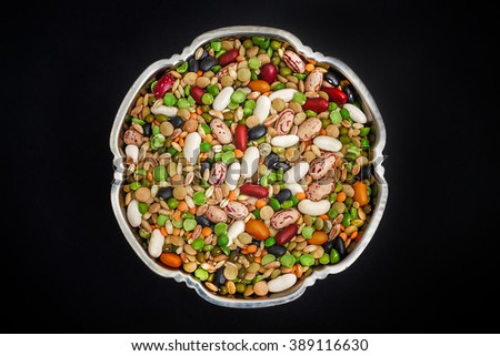 Mixed dried legumes and cereals in metallic bowl on black background. Top view