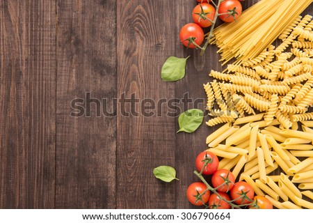 Mixed dried pasta selection on wooden background. - stock photo