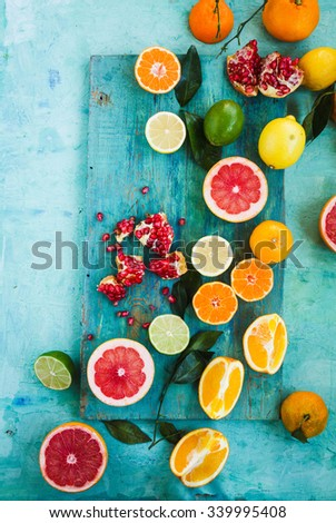 Mixed festive colorful tropical and citrus fruit sliced with leaves over light blue tabletop. Pastel rustic style.  - stock photo