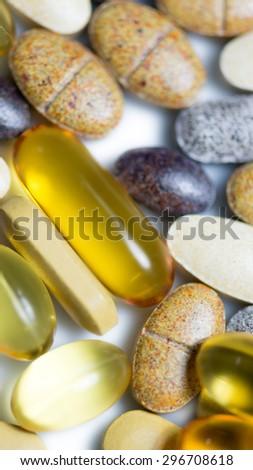 Mixed food supplement pills macro such as  fish oil capsules, vitamin pills , lutein tablet etc. consists of drug capsule. drug pill.Vitamin pills.CoQ10 pills.Vitamin C pills. - stock photo