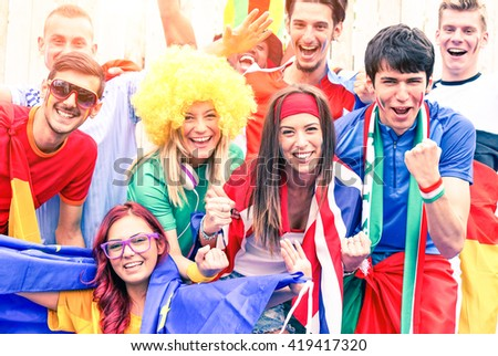Mixed football fans cheering together - Multiracial soccer supporters singing and screaming at stadium - Concept of brotherhood and friendship in sports and life - Main focus on right woman