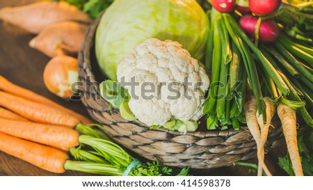 Mixed fresh and healthy raw vegetables ingredients of soup and other foods in wicker basket on dark brown wooden table background in the kitchen - stock photo