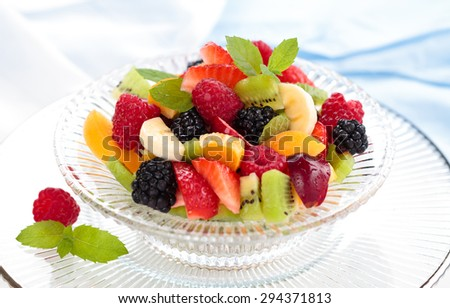 Mixed fresh fruits and mint leaves in glass bowl.