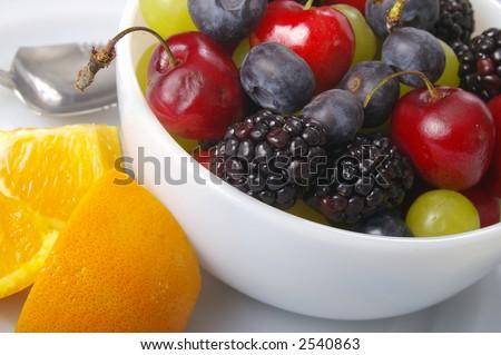 Mixed fresh fruits on crisp white serving dishes. - stock photo