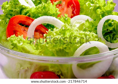 Mixed fresh salad with curly coral lettuce, white onions and red tomatoes - stock photo