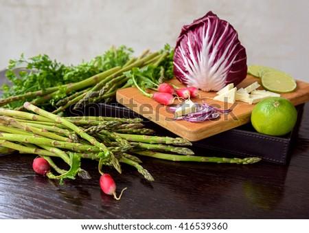 Mixed fresh spring vegetables: asparagus, radish, herbs, lime, cheese, mozzarella on a wooden table - stock photo