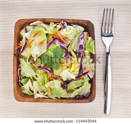 Mixed fresh vegetable salad in bamboo dish with fork on napkin  background - stock photo