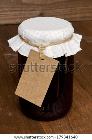 Mixed fruit jam in a glass jar with traditional cloth lid and blank label for insertion of your message or company branding. - stock photo