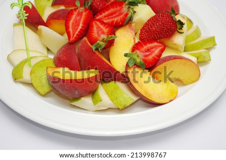 Mixed fruit salad in the bowl on white