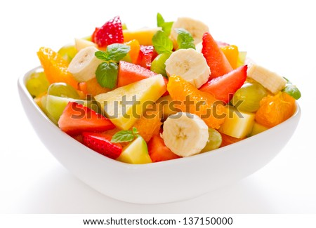 Mixed fruit salad in the bowl on white background - stock photo