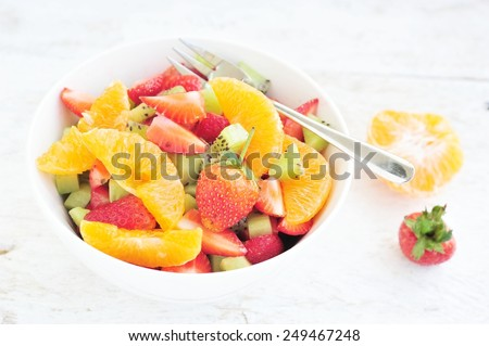 Mixed fruit salad in the bowl on white wood background. - stock photo