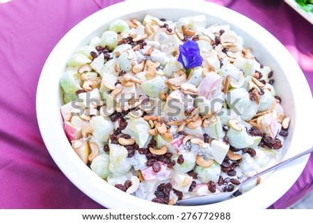 Mixed fruit salad in the bowl with cream salad dressing - stock photo
