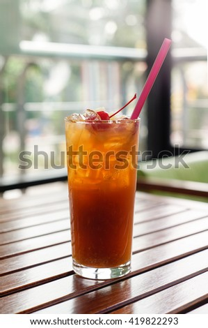 mixed fruits ice tea ingredients with cherry pineapple and papaya in glass on the wooden table background.