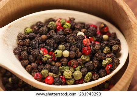 Mixed green, red, white and black peppercorns in a wooden spoon - stock photo