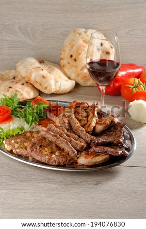 Mixed grill on a plate with excellent wine - stock photo