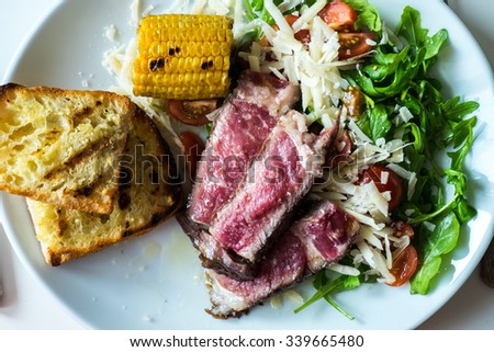 Mixed grill steak with corn and bread - stock photo