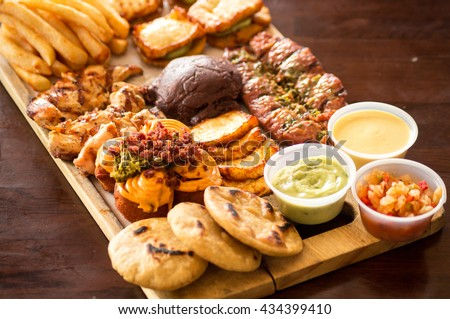 mixed Grilled meat with fries, smoked cheese, beans and vegetables on wood table
