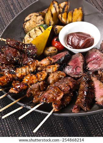 Mixed grilled meat with pepper sauce and Grilled vegetables on dark background - stock photo
