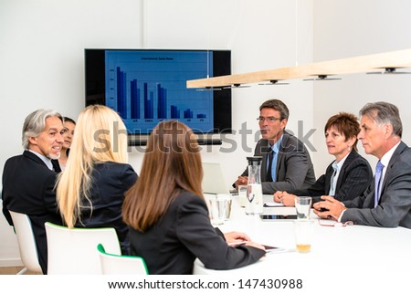 Mixed group in business meeting with laptops, projection screen, digital tablets and smartphones discussing the latest sales figures - stock photo