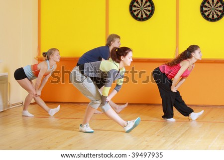 Mixed group making aerobics exercises in gym side-view