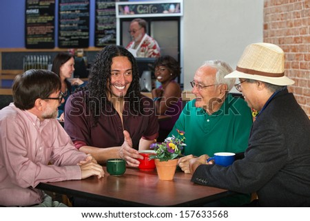 Mixed group of four adult men in cafe - stock photo