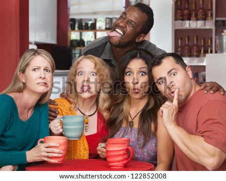 Mixed group of friends making faces in a cafe - stock photo