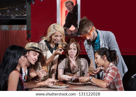 Mixed group of hipsters with pizza at food truck - stock photo