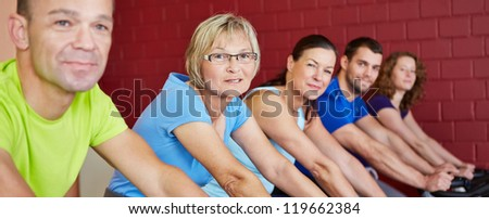 Mixed group riding bikes in spinning class in a health club - stock photo