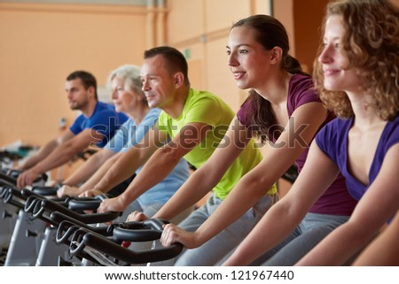 Mixed group riding bikes in spinning class in fitness center