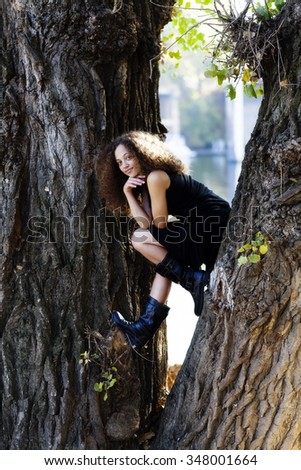 Mixed Heritage Woman Black Dress Sitting In Tree