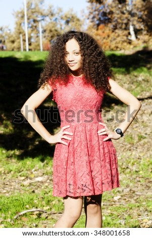 Mixed Heritage Woman Red Dress Standing On Grass