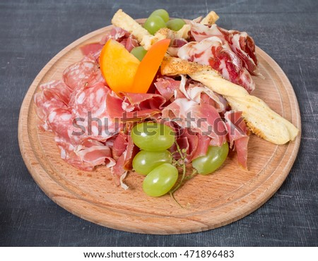 Mixed italian dried meats platter with croutons and grapes. Plate located on a black table as a background.