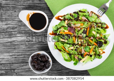 mixed lettuce, spinach, carrot, ham. cheese and prunes salad on a white dish, simply and healthy recipe, top view - stock photo