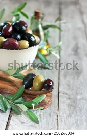 Mixed marinated olives (green, black and purple) in ceramic bowl and wooden spoon with bottle of olive oil. Selective focus. Copy space background - stock photo