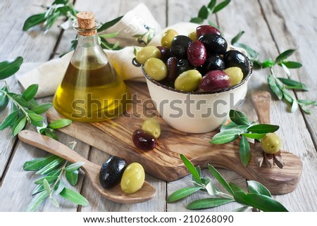 Mixed marinated olives (green, black and purple) in ceramic bowl and wooden spoon with bottle of olive oil. Selective focus. - stock photo