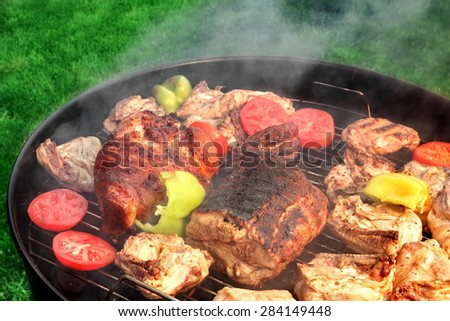 Mixed Meat And Vegetables On The Hot BBQ Charcoal Grill. Pork Ribs, Knuckle, Chicken Cuts, Paprika, Tomato