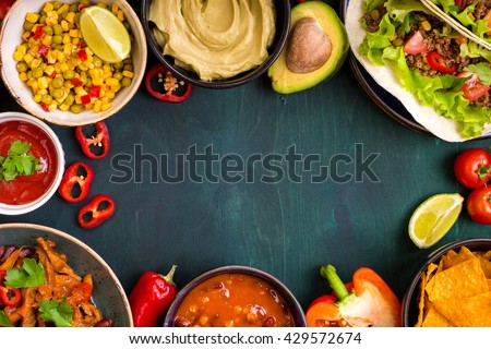 Mixed mexican food background. Party food. Guacamole, nachos, fajita, meat tacos, salsa, peppers, tomatoes on a wooden table. Space for text. Top view. Tex-mex cuisine. Assorted appetizers. Food frame - stock photo