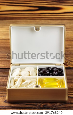 Mixed natural food supplement pills in container, omega 3, vitamin c, carotene capsules, on wooden background - stock photo