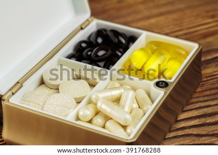 Mixed natural food supplement pills in container, omega 3, vitamin c, carotene capsules, on wooden background, selective focus - stock photo