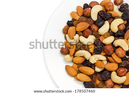 Mixed nuts and dry fruits in plate isolated on white background close-up - stock photo