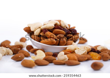 Mixed nuts and sultanas on a plate on a white background