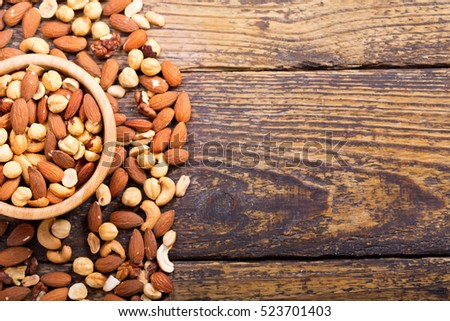 mixed nuts in a bowl on wooden table, top view with copy space.