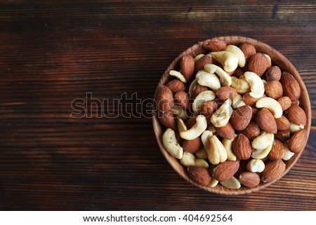Mixed nuts in a wood bowl on a wooden background. Text space. Flat lay. Close up. - stock photo