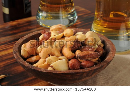 Mixed nuts on a bar counter with tall glasses of beer - stock photo